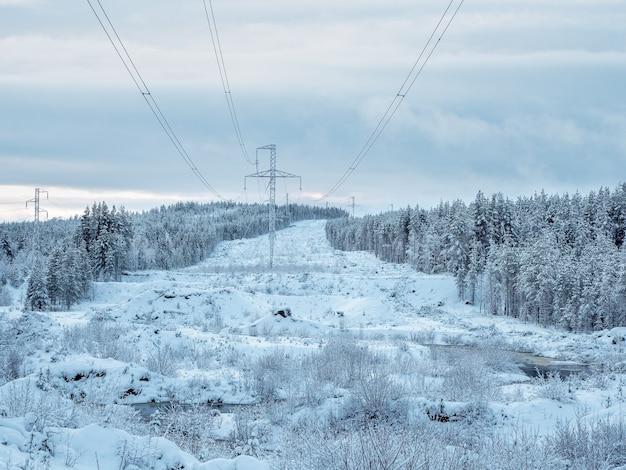 Torres de energia nas montanhas do norte cobertas de neve.