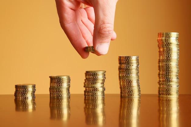 Torres de moedas de ouro na mesa e na mão