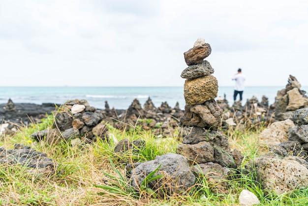 Torres de pedra em rochas basálticas na praia de hyeopjae, ilha de jeju