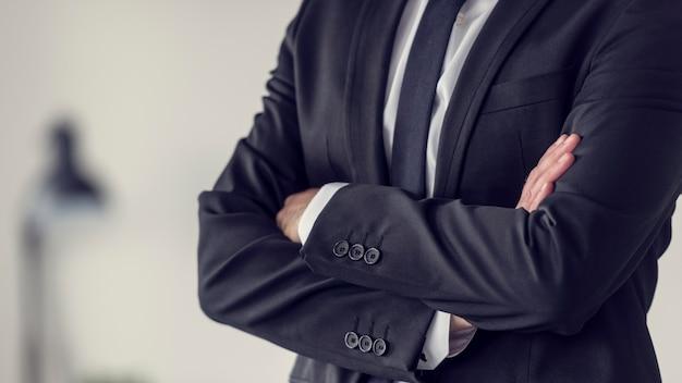Torso de um empresário em pé com os braços cruzados