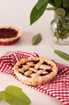 Torta aberta de massa quebrada com cerejas e framboesas, uma torta com guardanapo em um fundo branco