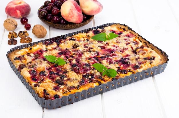 Torta caseira com frutas, frutas e nozes em forma de luz de fundo.