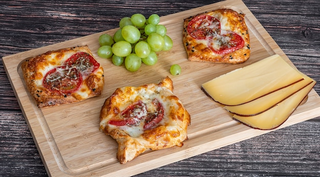 Torta caseira com tomate e queijo repousa sobre uma tábua de madeira ao lado das uvas e pedaços de queijo