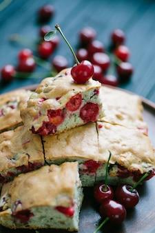 Torta caseira de cereja em um prato e fundo de madeira