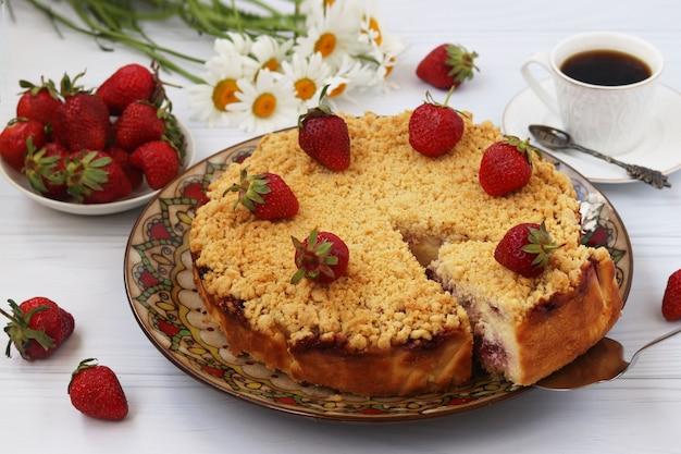 Torta caseira de morango em um prato sobre uma superfície branca, com um pedaço de bolo recortado, close, formato horizontal