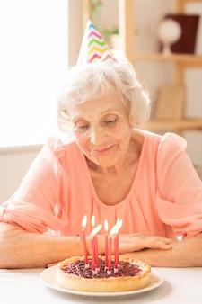 Torta caseira fresca com velas acesas no prato, preparada para o aniversário da terceira idade