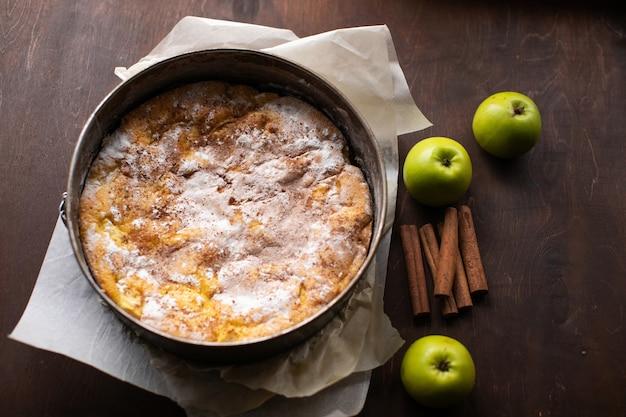 Torta caseira, maçãs verdes e paus de canela na mesa de madeira marrom