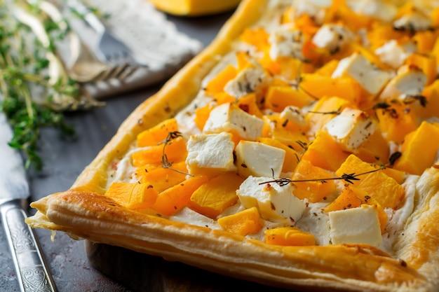 Torta com abóbora, queijo feta, ricota e tomilho sobre um fundo escuro de concreto.