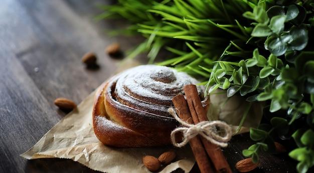 Torta com canela e maçãs em uma mesa de madeira. pastelaria fresca com paus de canela com nozes e açúcar em pó. pão com nozes e canela na mesa.