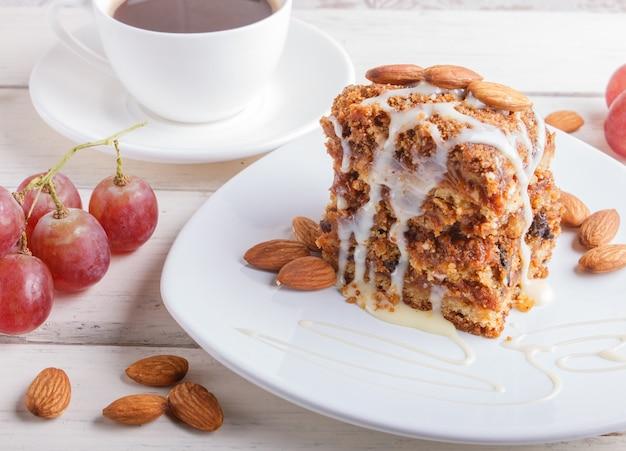 Torta com caramelo, molho de leite branco e amêndoas em um prato branco