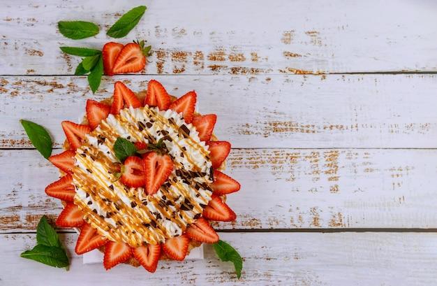 Torta com chantilly e morangos na superfície de madeira branca