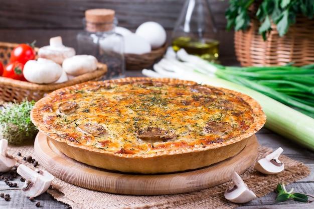 Torta com cogumelos, frango na mesa de madeira da cozinha
