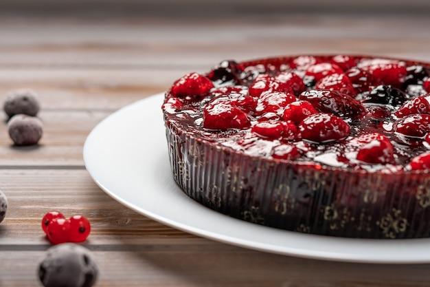 Torta com frutas closeup framboesa groselha morango em um prato branco sobre um fundo de madeira perto
