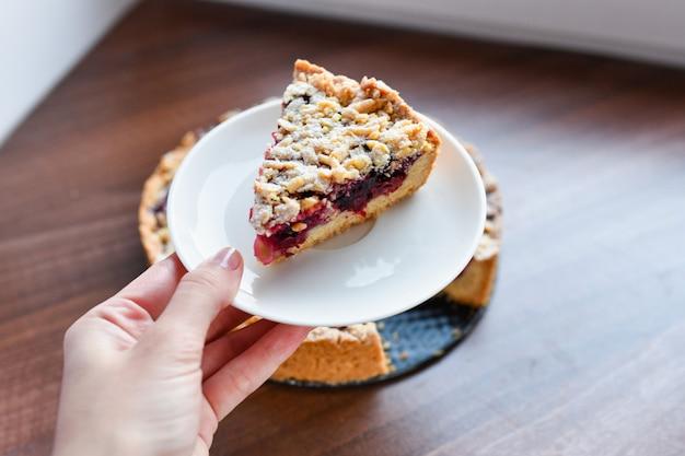 Torta com frutas: framboesas, morangos, groselhas, num prato branco, a mão de uma mulher segurando um pedaço de bolo em uma espátula. sobre um fundo de madeira, no guardanapo de linho de fundo