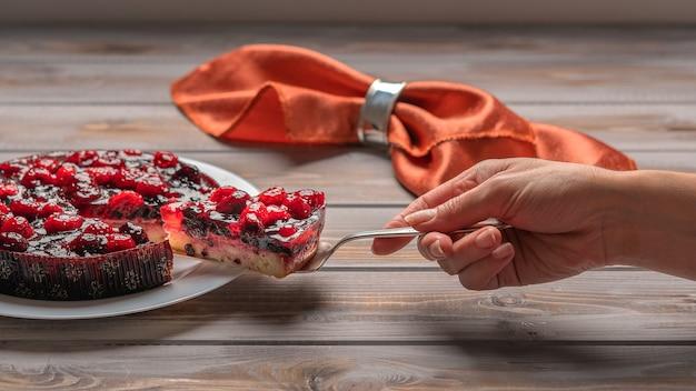 Torta com frutas vermelhas, framboesas, morangos, groselha na mão de uma mulher de planalto branco segurando um pedaço de