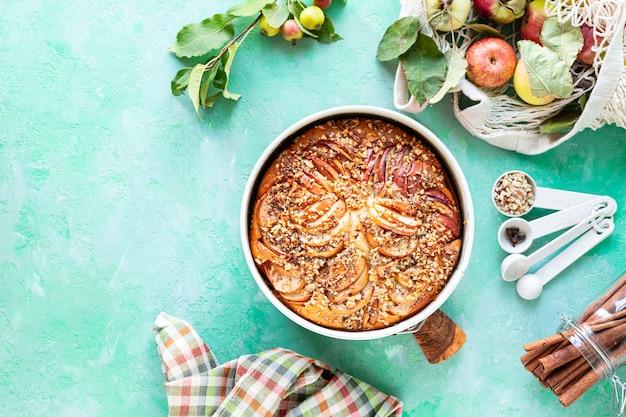Torta com maçãs e ingredientes em um fundo de pedra verde. vista do topo. copie o espaço.