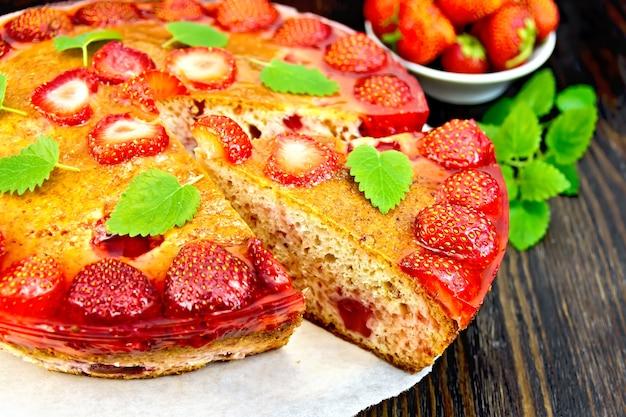 Torta com morango, beijinho, geléia e hortelã em um fundo de pergaminho na placa de madeira