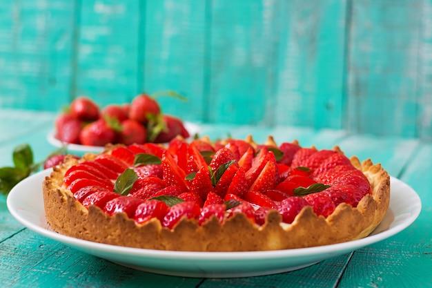 Torta com morangos e chantilly decorado com folhas de hortelã.