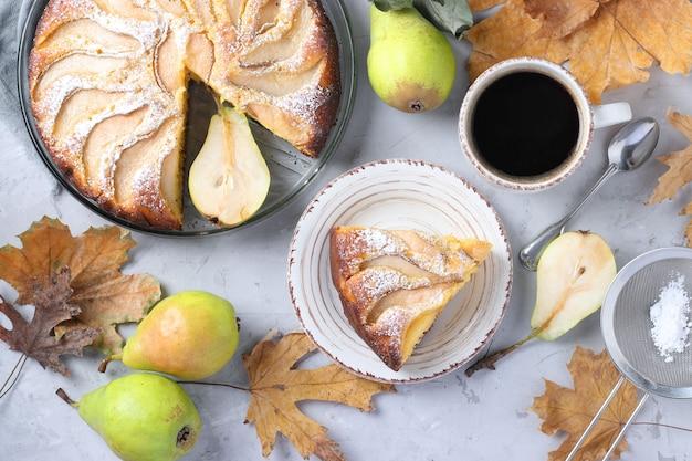 Torta com peras, xícara de café e folhas de outono em cinza, vista de cima