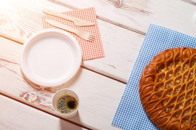 Torta com prato e talheres. beba e torta no guardanapo. saboroso café da manhã no bistrô. café quente e pastelaria fresca.