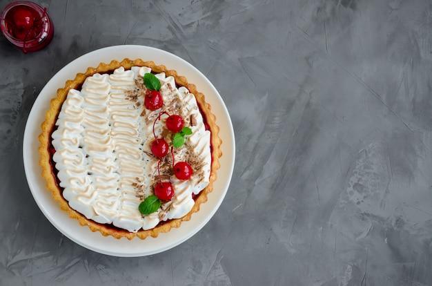 Torta com recheio de cereja e merengue italiano com uma cereja de coquetel