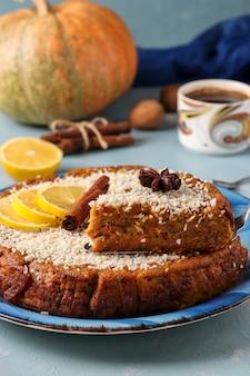 Torta de abóbora caseira com limão, canela e nozes, polvilhada com coco, cortada, sobre uma superfície azul clara com uma xícara de café