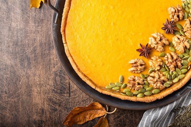 Torta de abóbora caseira fresca de ação de graças decorada com nozes e sementes em uma bandeja vintage