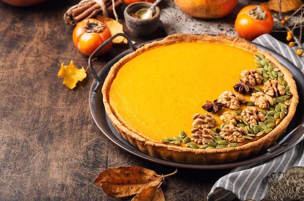 Torta de abóbora caseira fresca de ação de graças, decorada com nozes e sementes na bandeja vintage em fundo de madeira compensada rústica.