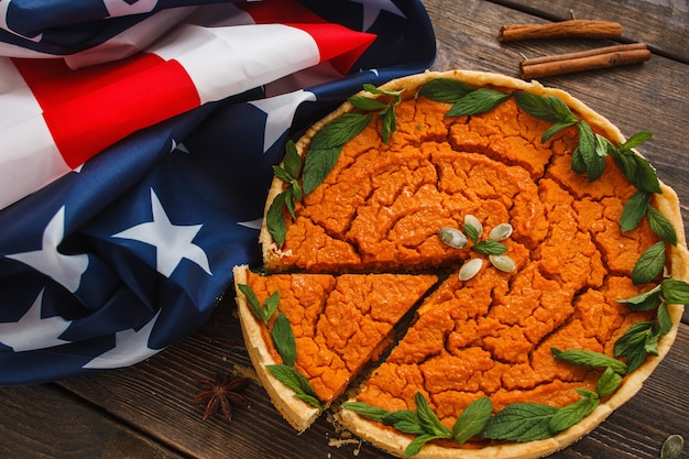 Torta de abóbora com bandeira americana plana leigos. composição patriótica de bandeira nacional e torta de abóbora tradicional, doce de ação de graças