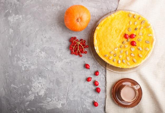 Torta de abóbora doce americana tradicional, decorada com bagas de espinheiro vermelho e sementes de abóbora com uma xícara de café sobre um fundo cinza de concreto