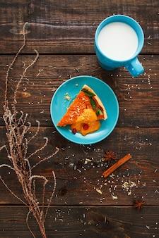 Torta de abóbora doce laranja com copo turquesa brilhante de leito plano. vista superior da linda sobremesa doce servida com bebida em estilo rústico