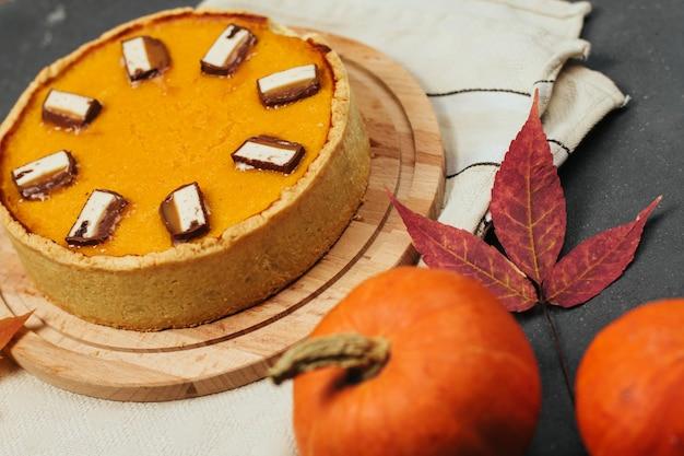 Torta de abóbora em uma placa de madeira, folhas de outono e pequenas abóboras em um fundo cinza escuro.
