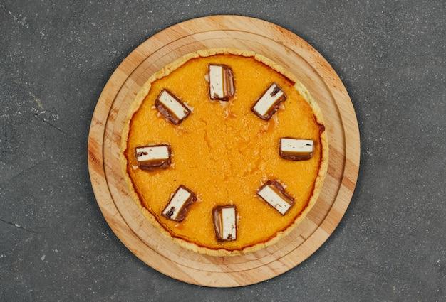 Torta de abóbora em uma placa de madeira sobre um fundo cinza escuro. deleite do dia das bruxas.