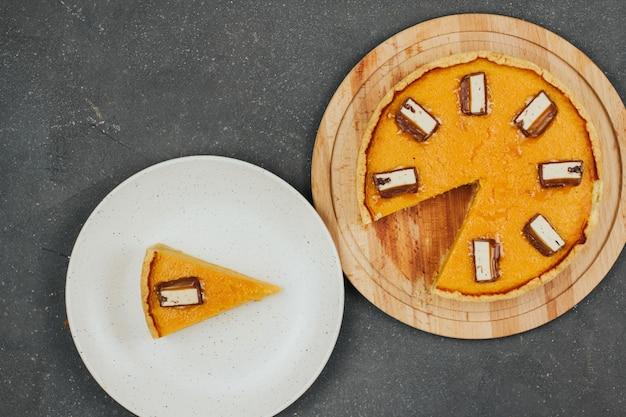 Torta de abóbora em uma tábua de madeira redonda e um pedaço de bolo em um prato branco.