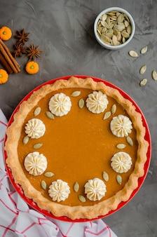 Torta de abóbora festiva tradicional com especiarias, chantilly e sementes por cima em um fundo de pedra escuro. sobremesa de ação de graças.