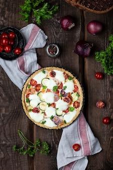 Torta de abobrinha caseira e tomate cereja com mussarela em fundo de madeira