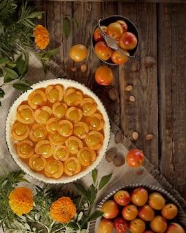 Torta de abricó cru antes de assar. damascos e malmequeres na mesa de madeira. vista do topo