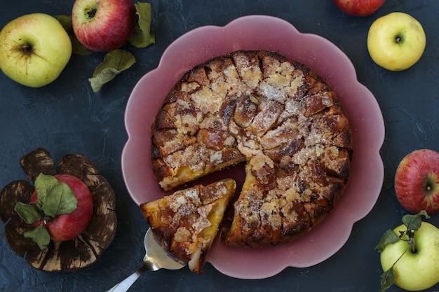 Torta de açúcar caseira com maçãs em um fundo escuro em um prato rosa, vista de cima, orientação horizontal