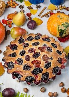 Torta de ameixa em um fundo de outono claro, com folhas caídas, frutas, nozes, abóbora. lay plana.
