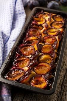 Torta de ameixa na assadeira na mesa de madeira