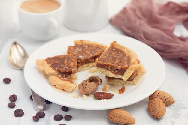 Torta de amêndoa em um pequeno prato e xícara de café