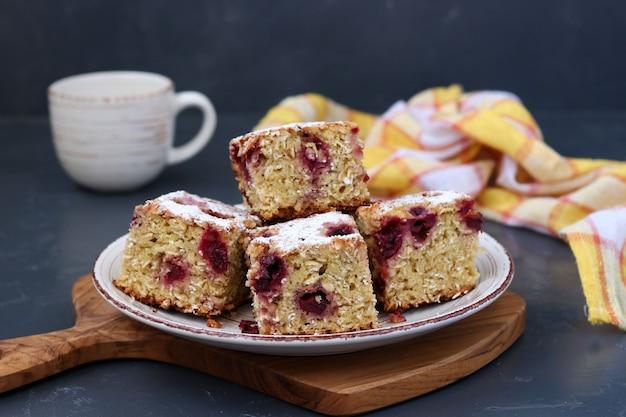 Torta de aveia fatiada com cereja polvilhada com açúcar em pó num prato sobre um fundo escuro