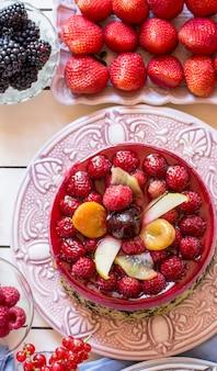 Torta de bagas saborosa no carrinho do bolo rosa