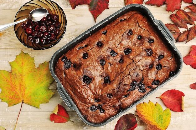 Torta de brownie com cerejas em um fundo de madeira com folhas de outono - vista superior
