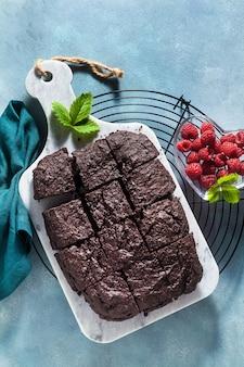 Torta de brownie de chocolate vegan com tahine e framboesas frescas em um fundo azul