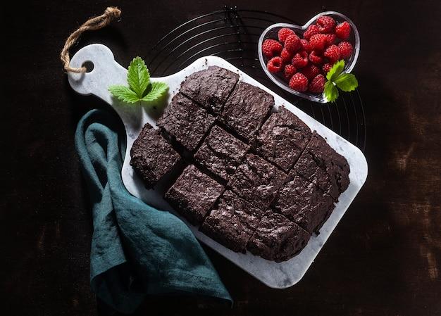 Torta de brownie de chocolate vegan com tahine e framboesas frescas em um fundo escuro