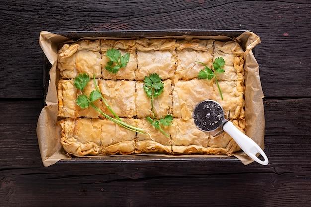 Torta de carne australiana fresca com coentro em uma tabela de madeira. estilo rústico,