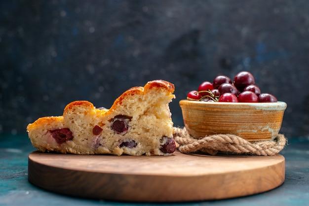 Torta de cereja fatiada junto com cerejas frescas em um bolo de frutas escuro