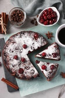 Torta de chocolate caseira com cerejas em um fundo cinza. vista de cima