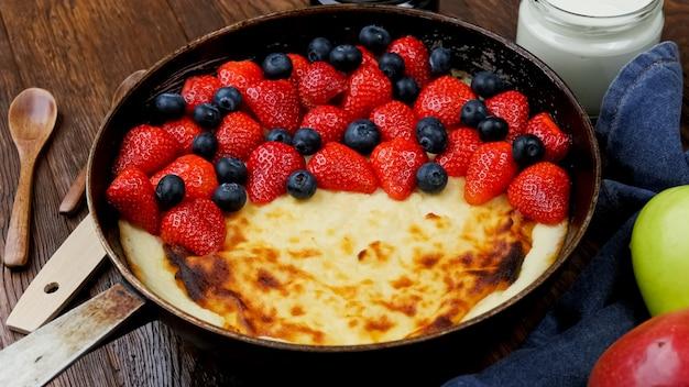 Torta de coalhada frita em uma frigideira com morangos e mirtilos em uma mesa de madeira